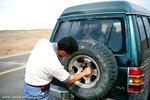 郭师父 was putting back on the flat tire.